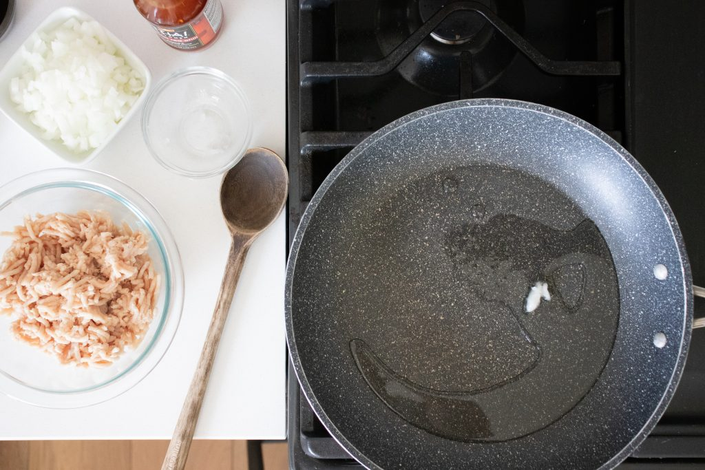 adding oil to frying pan image chicken lettuce cups